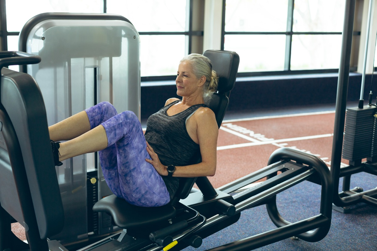 Older woman using the leg press machine at the gym