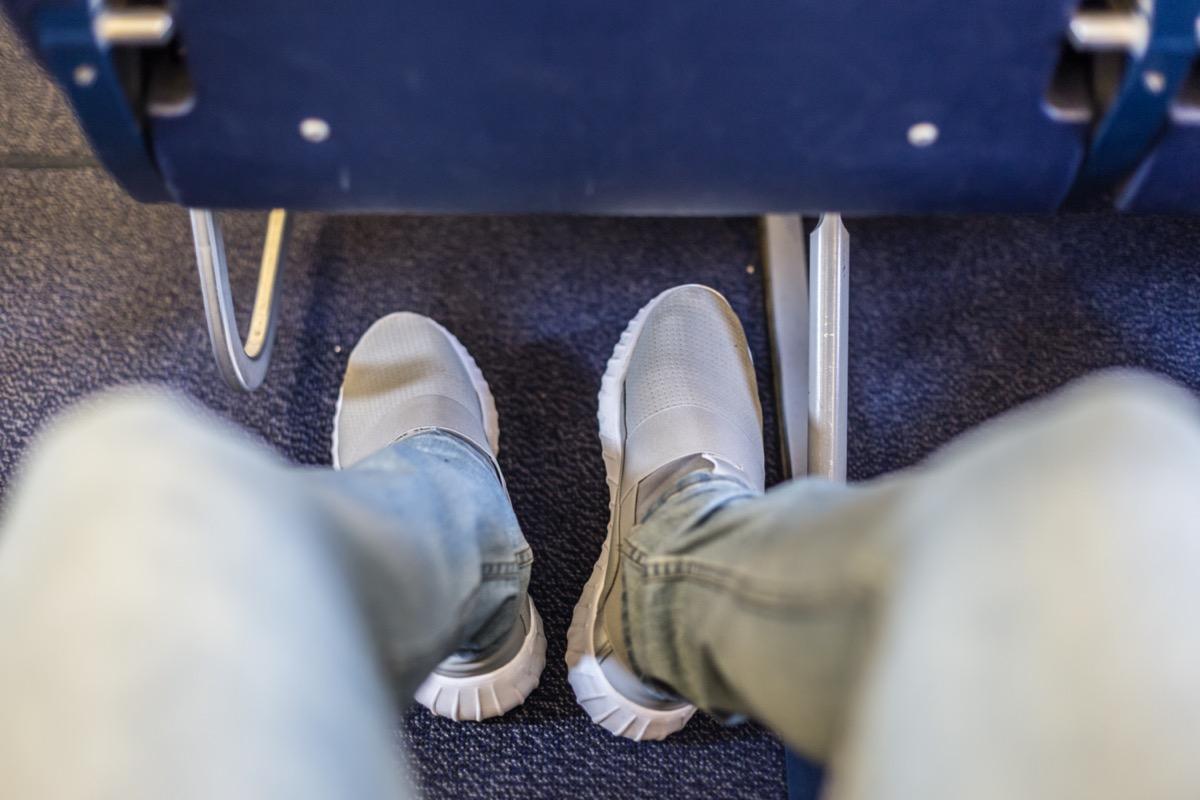 man's shoes underneath a plane seat