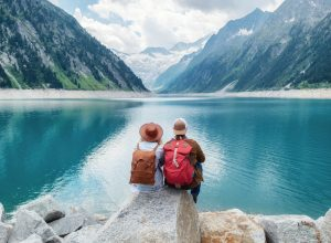 backpacking couple surveys romantic lake surrounded by mountains