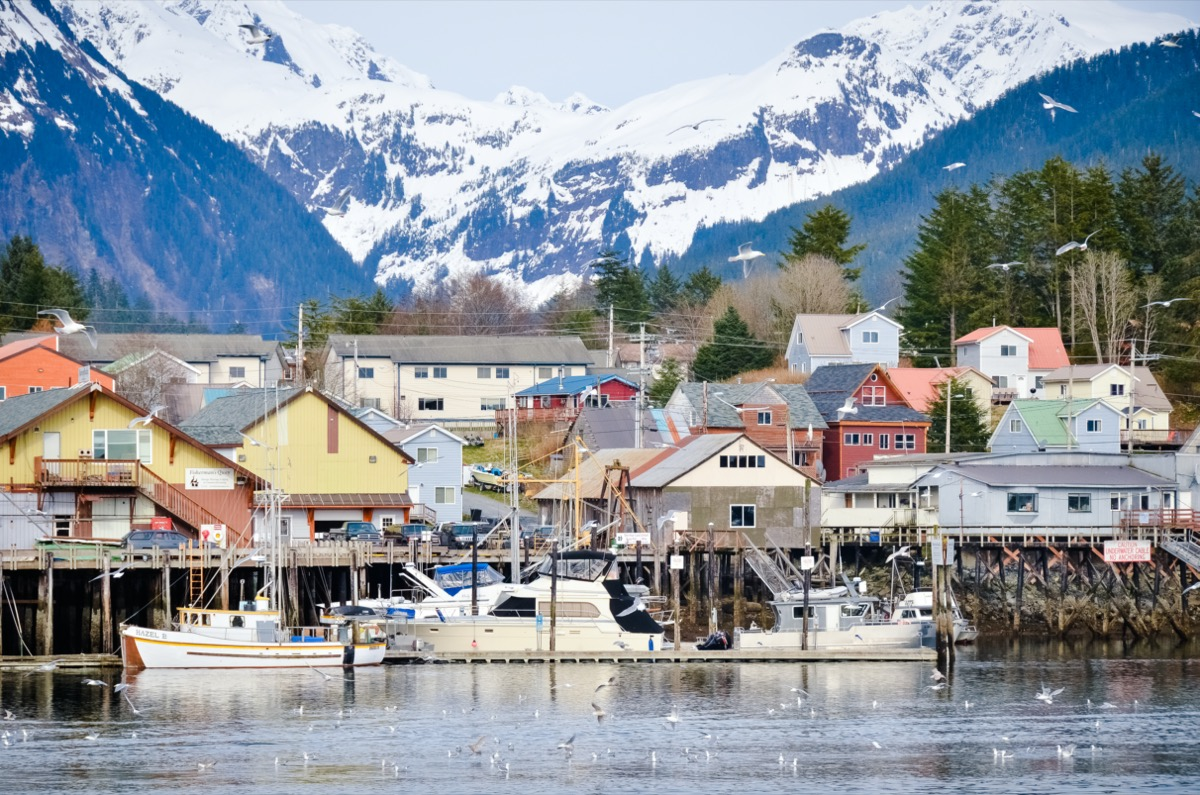 colorful buildings on a harbor with snowy mountains in the background