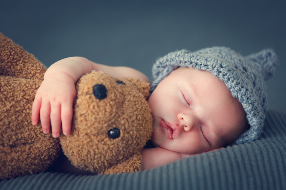 sleeping newborn baby with teddy