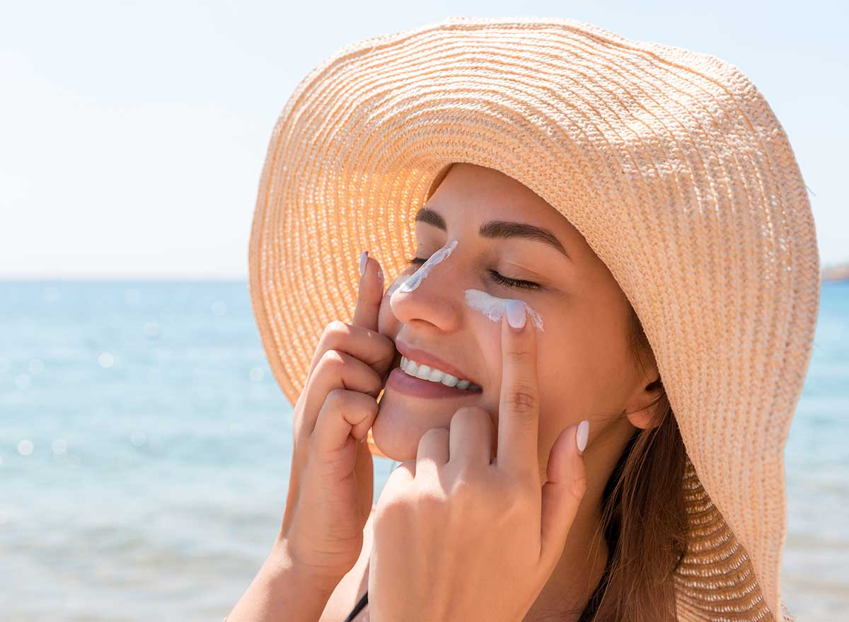 woman putting on sunscreen at the beach
