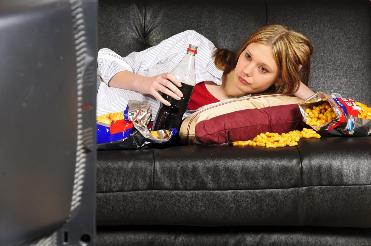 Girl snacking on couch while watching tv