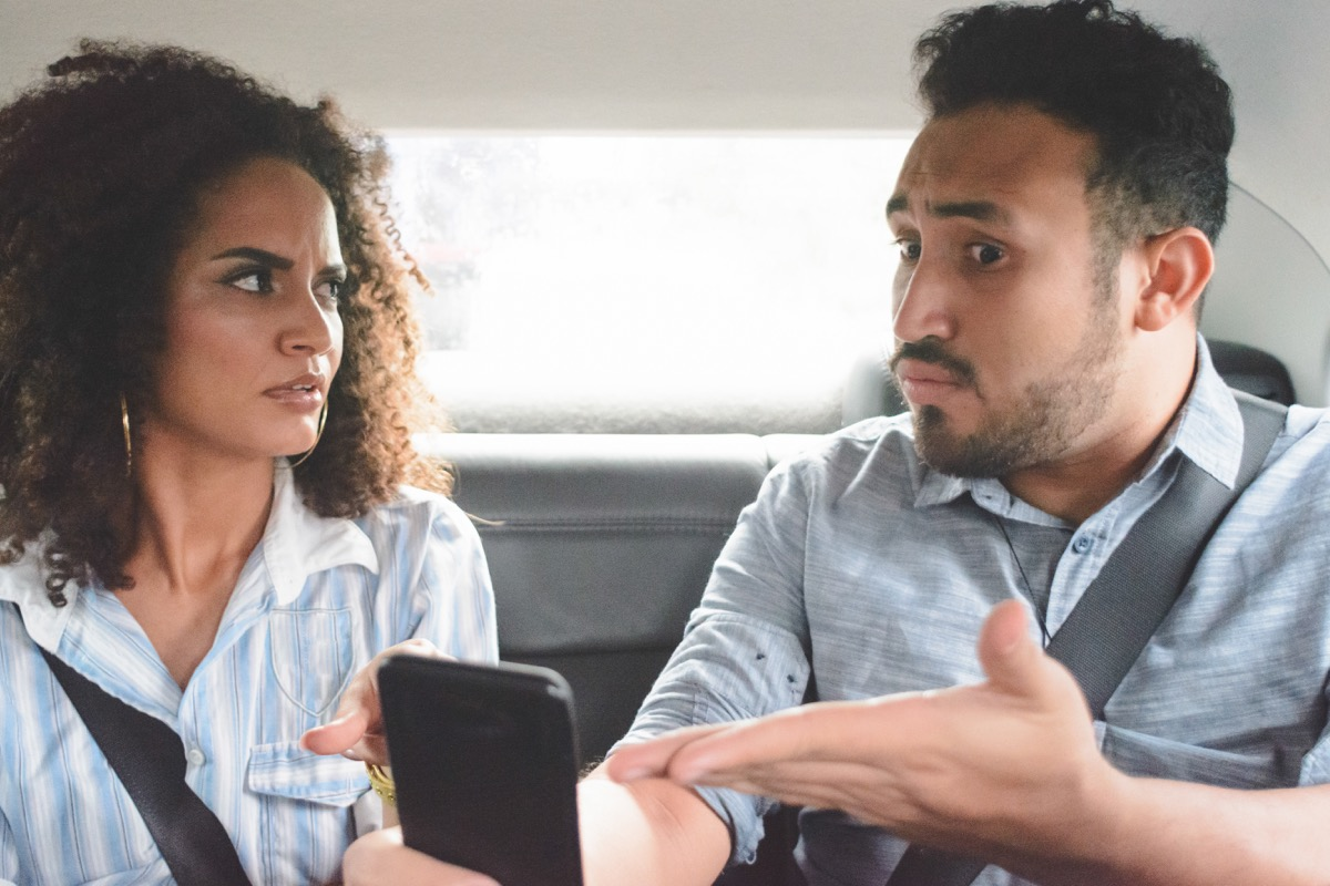 young couple with relationship problems arguing in the backseat of a car