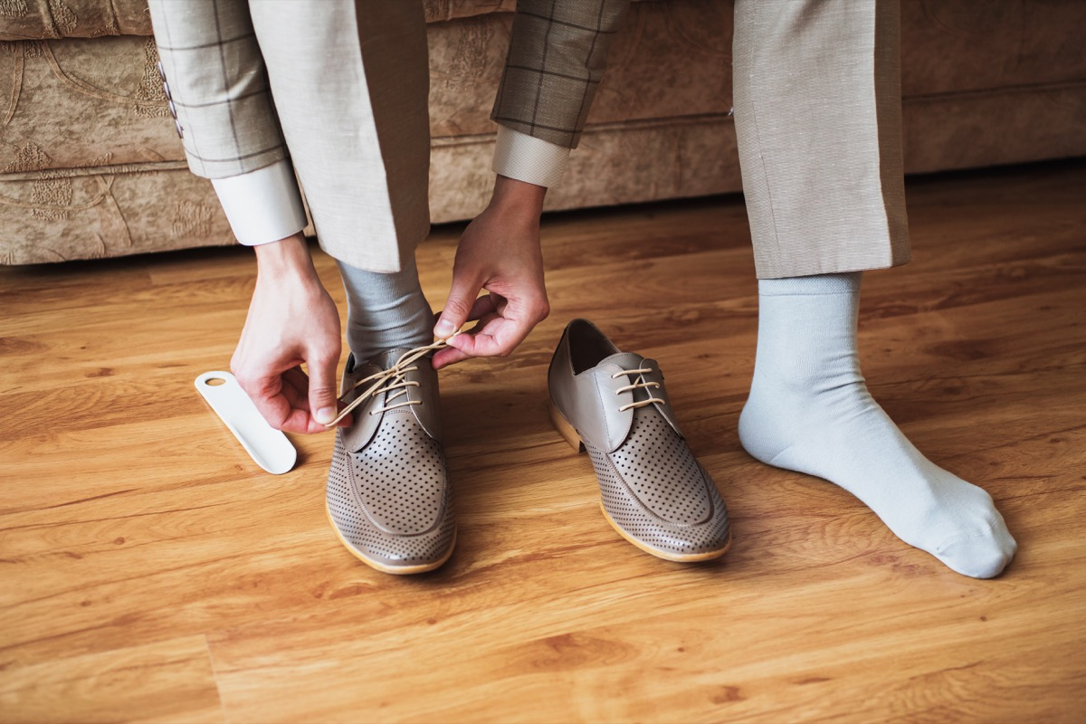 Man putting on socks and dress shoes