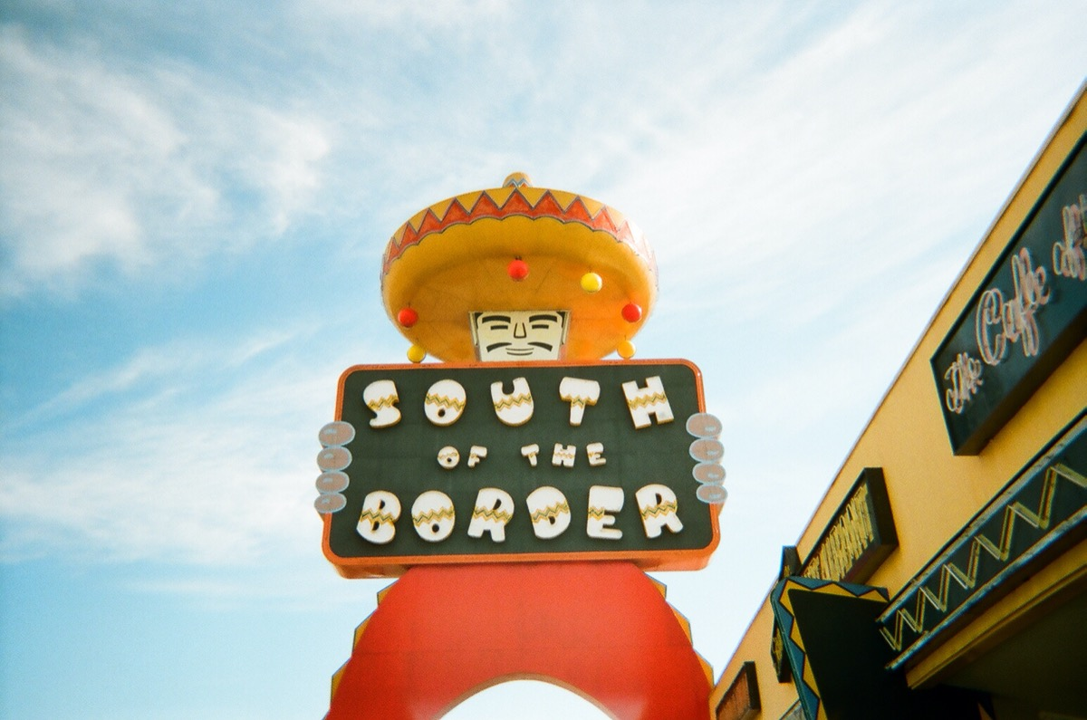 statue of man holding south of the border sign