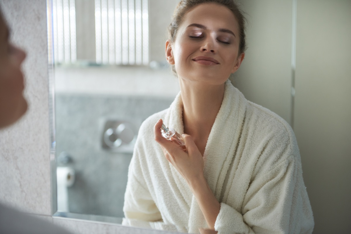 Self care concept. Waist up reflection of young smiling woman in white bathrobe enjoying her morning while applying favorite perfume before bathroom mirror (Self care concept. Waist up reflection of young smiling woman in white bathrobe enjoying her m