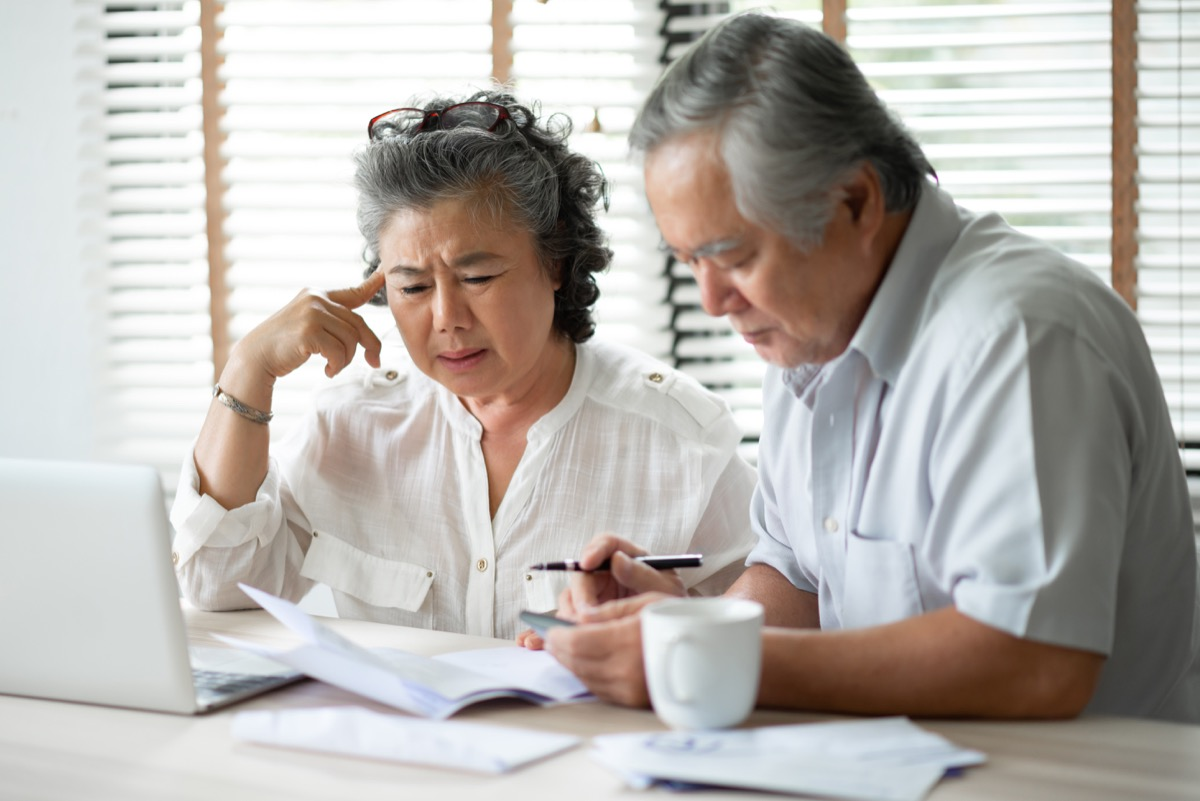 serious asian couple looking stressed and annoyed overpaper work