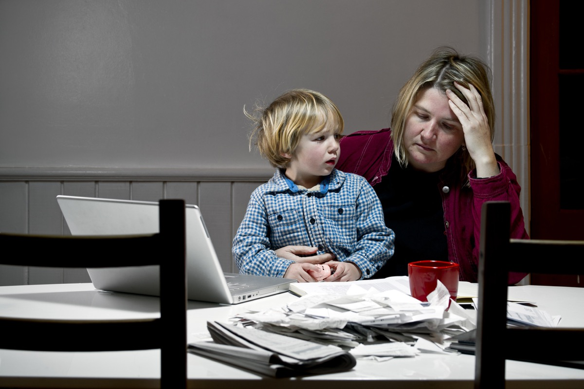 Depressed woman with son in lap at table, overwhelmed with financial issues, debt, bankruptcy.