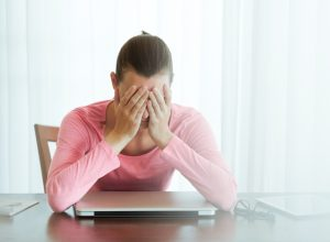 stressed out 30-something white woman sitting with face in hands over laptop