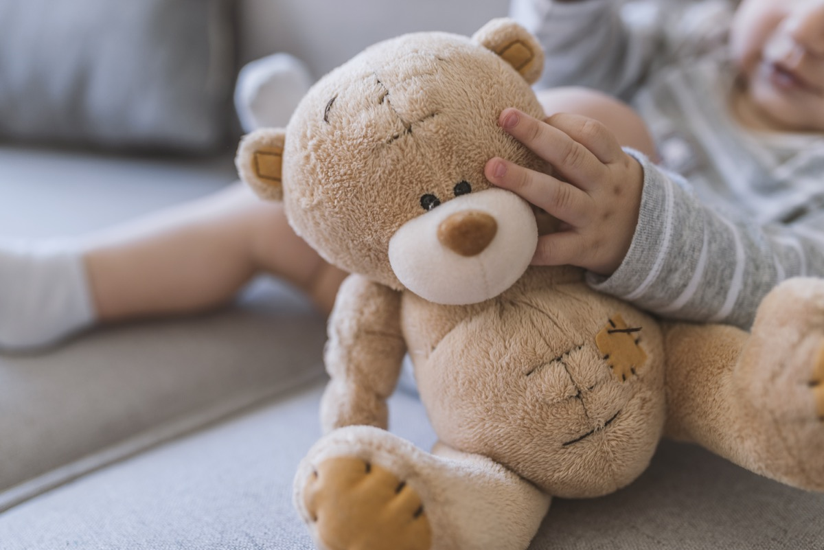 baby hands holding a teddy bear. Baby in bed, holding a teddy bear