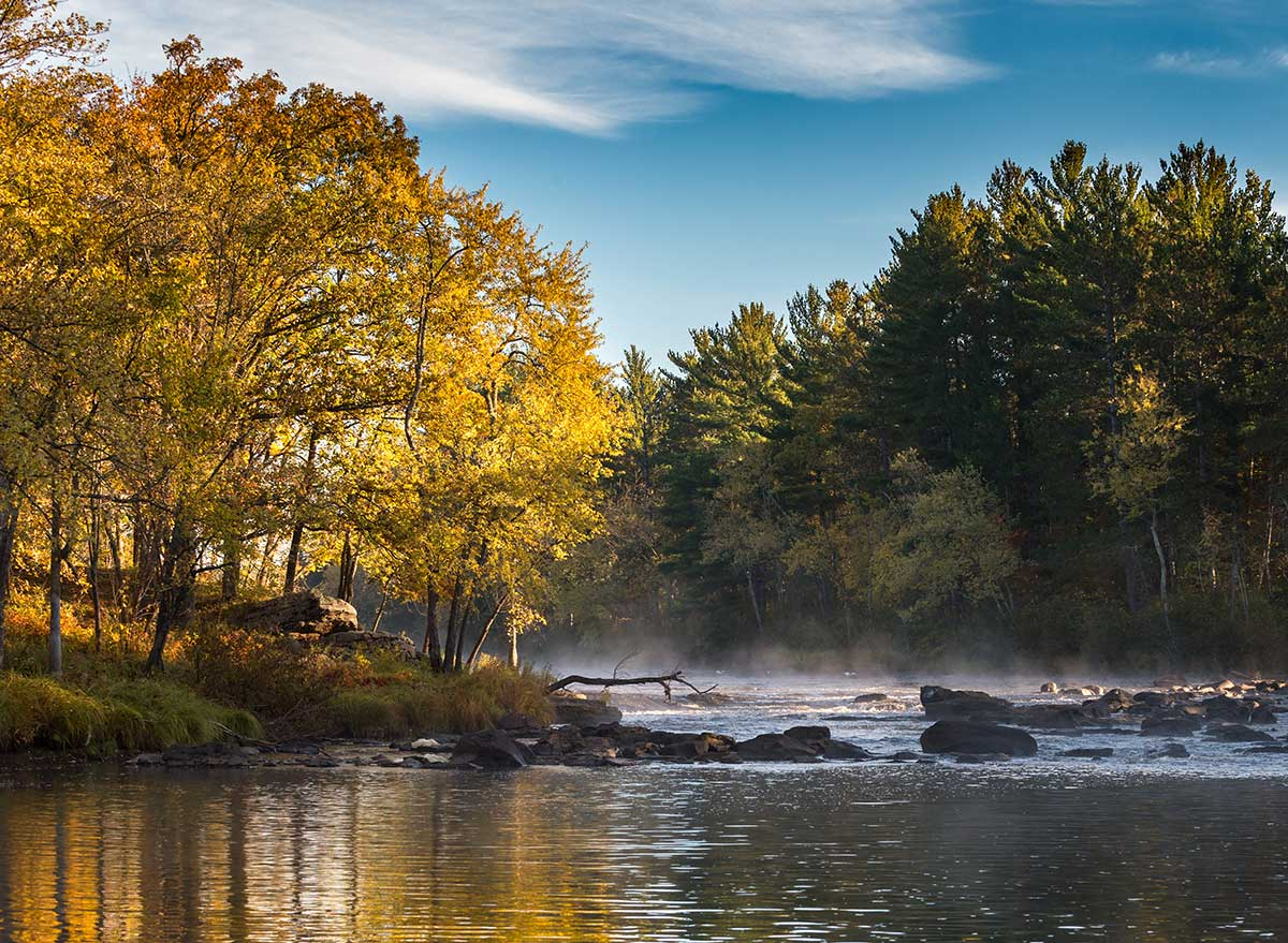 river with mist coming off of it during fall foliage