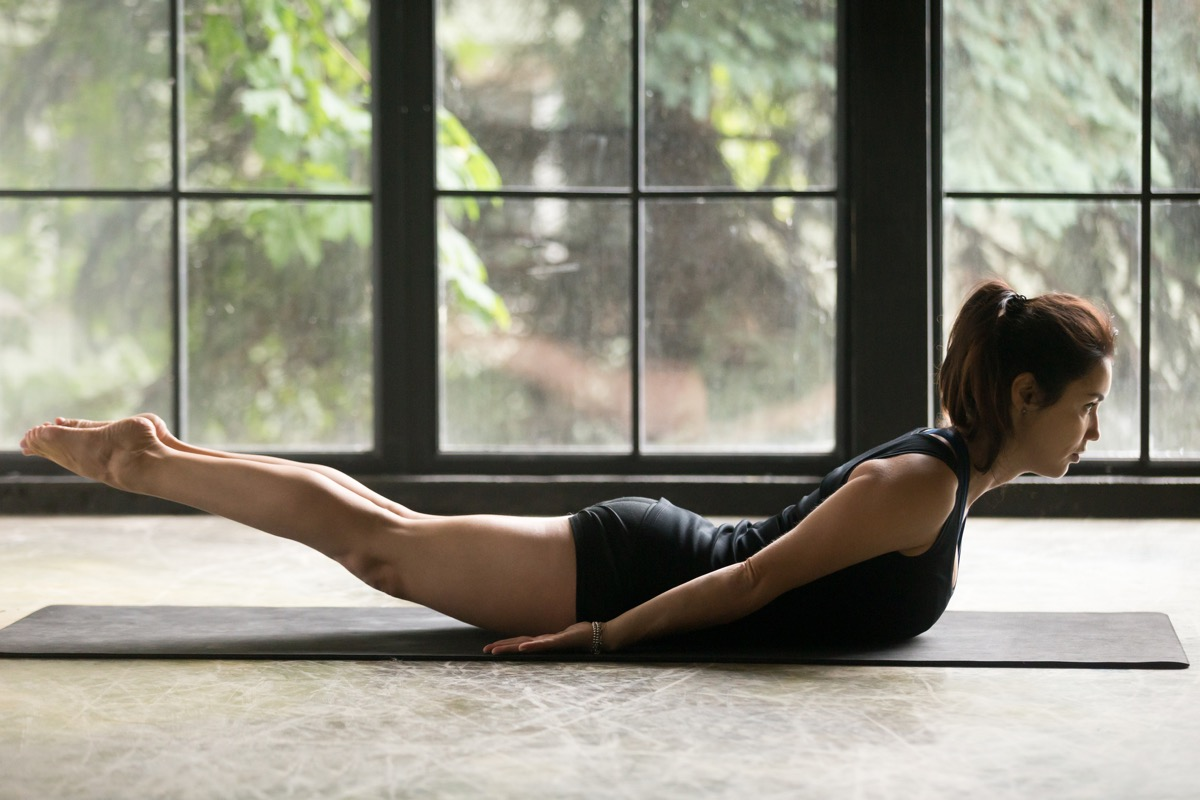 Young attractive woman practicing yoga at home, stretching in Salabhasana exercise, Double Leg Kicks pose, working out, wearing sportswear, black shorts and top, indoor full length, studio background (Young attractive woman practicing yoga at home, st