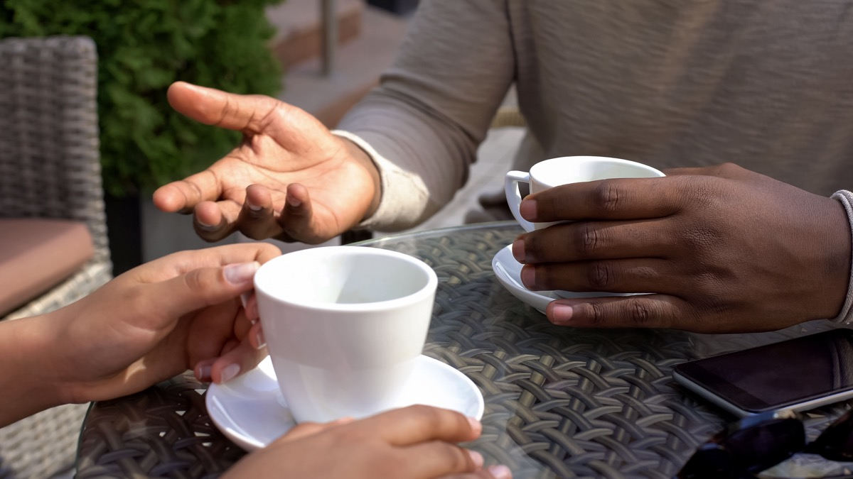 black man talking to woman sitting in cafe, colleagues drinking coffee together