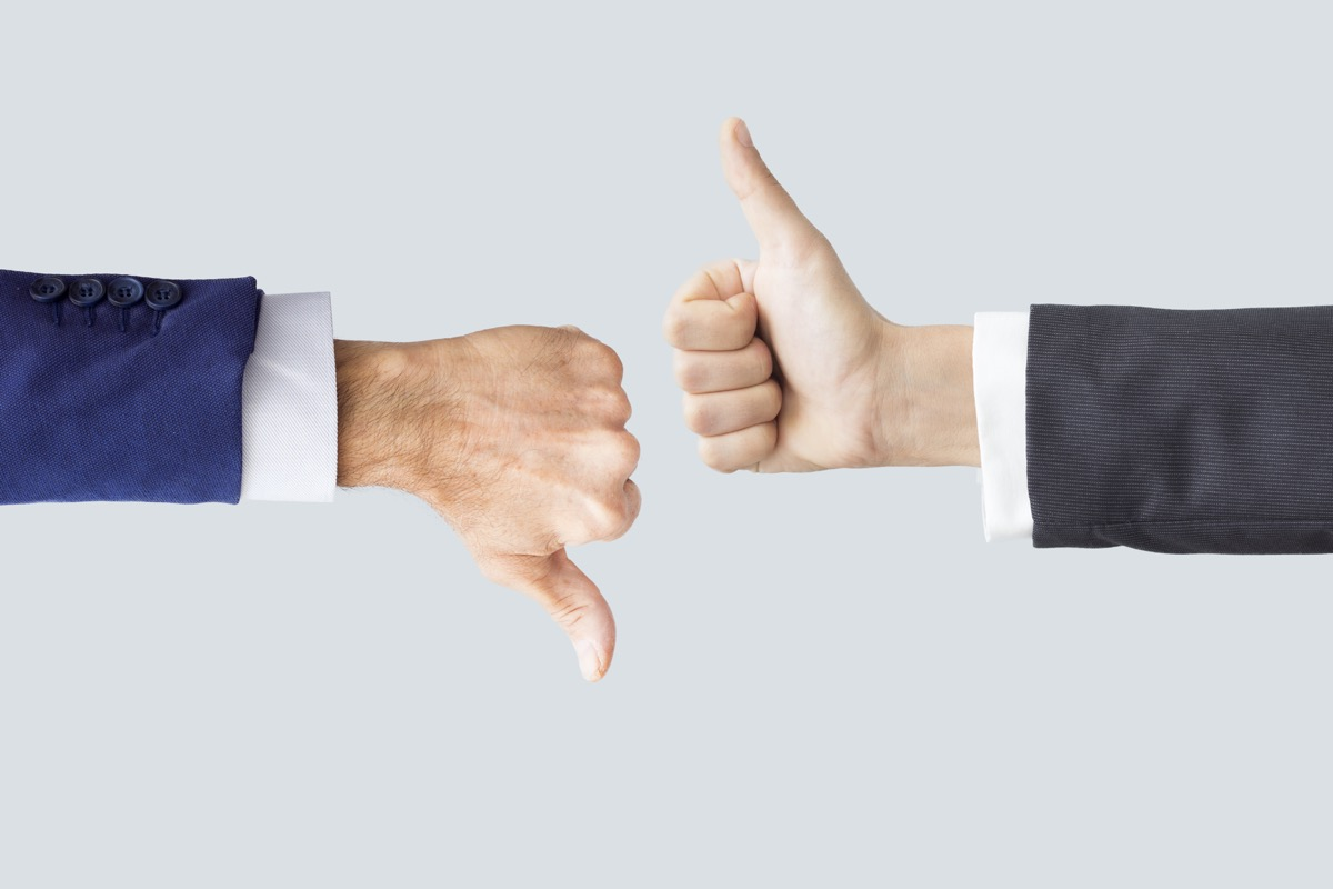 Hands making thumbs up and down
