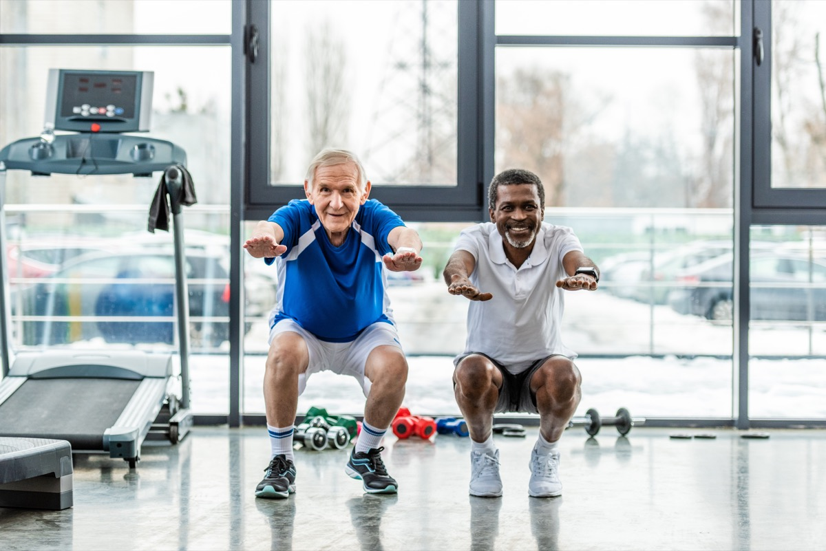 two seniors doing squats at the gym
