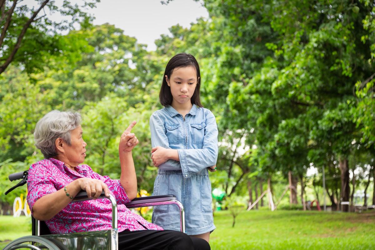 upset grandmother in wheelchair scolding granddaughter