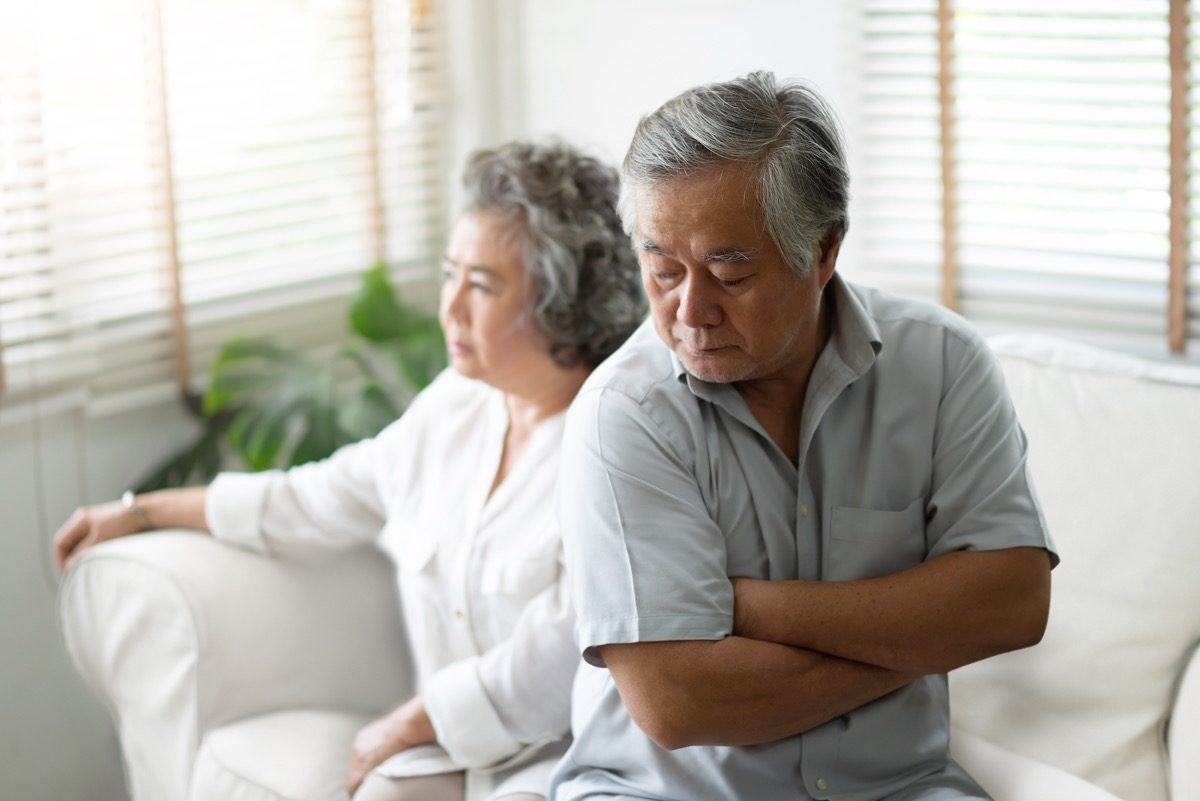 older asian couple sitting on couch looking upset and angry