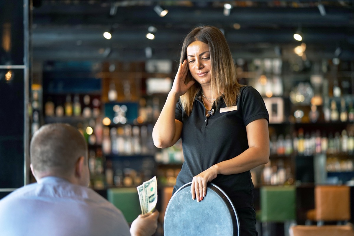 waitress holding tray and looking upset