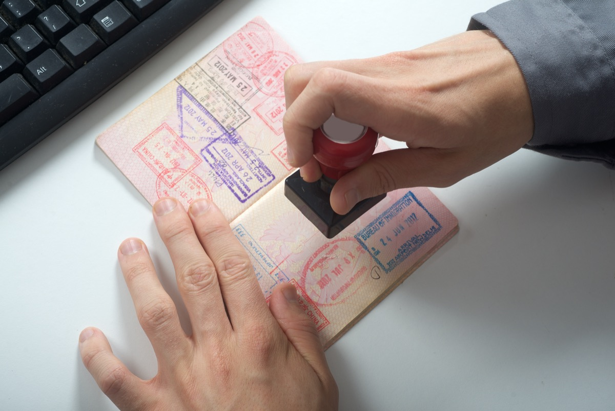 immigration officer putting stamp on passport