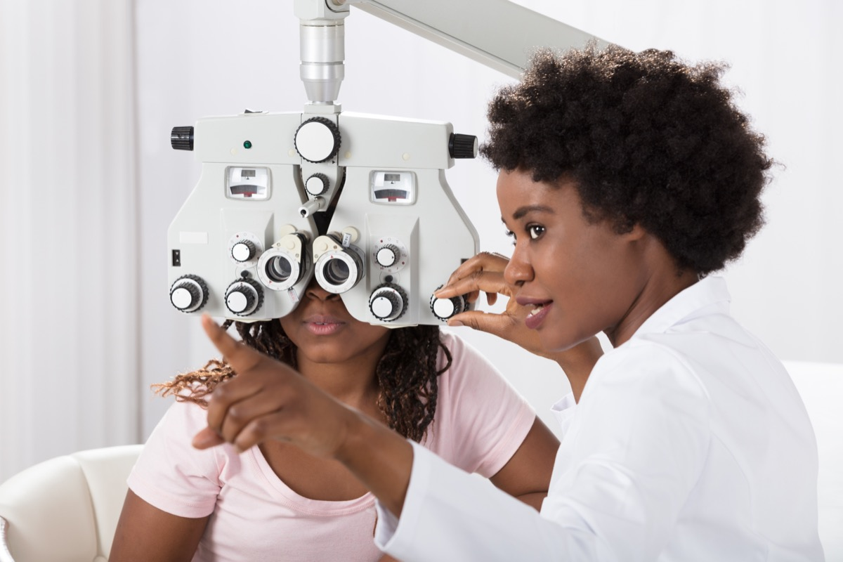 black woman doctor administering eye test to young patient