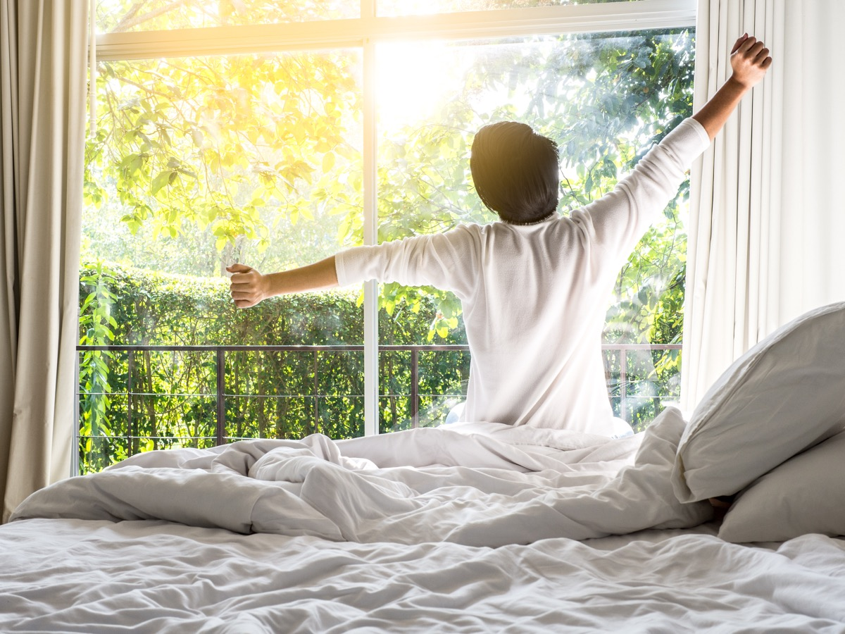 Person stretching in bed and waking up early