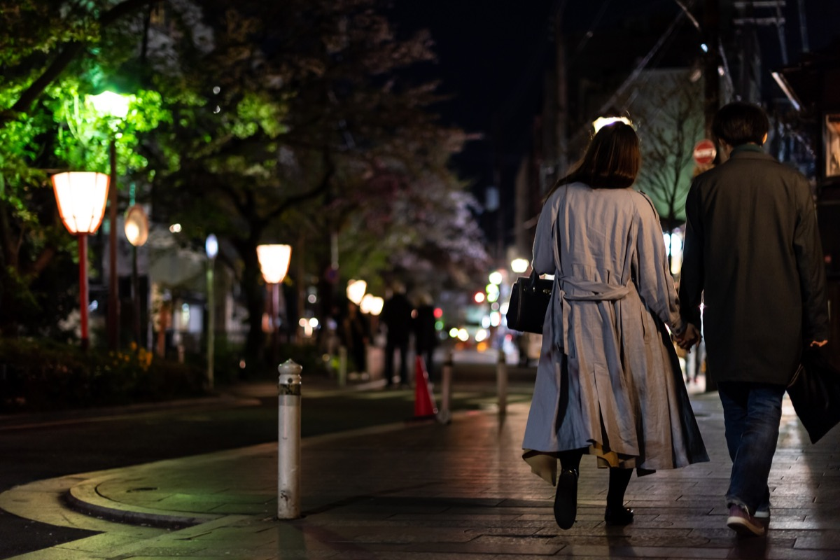 Couple holding hands walk at night