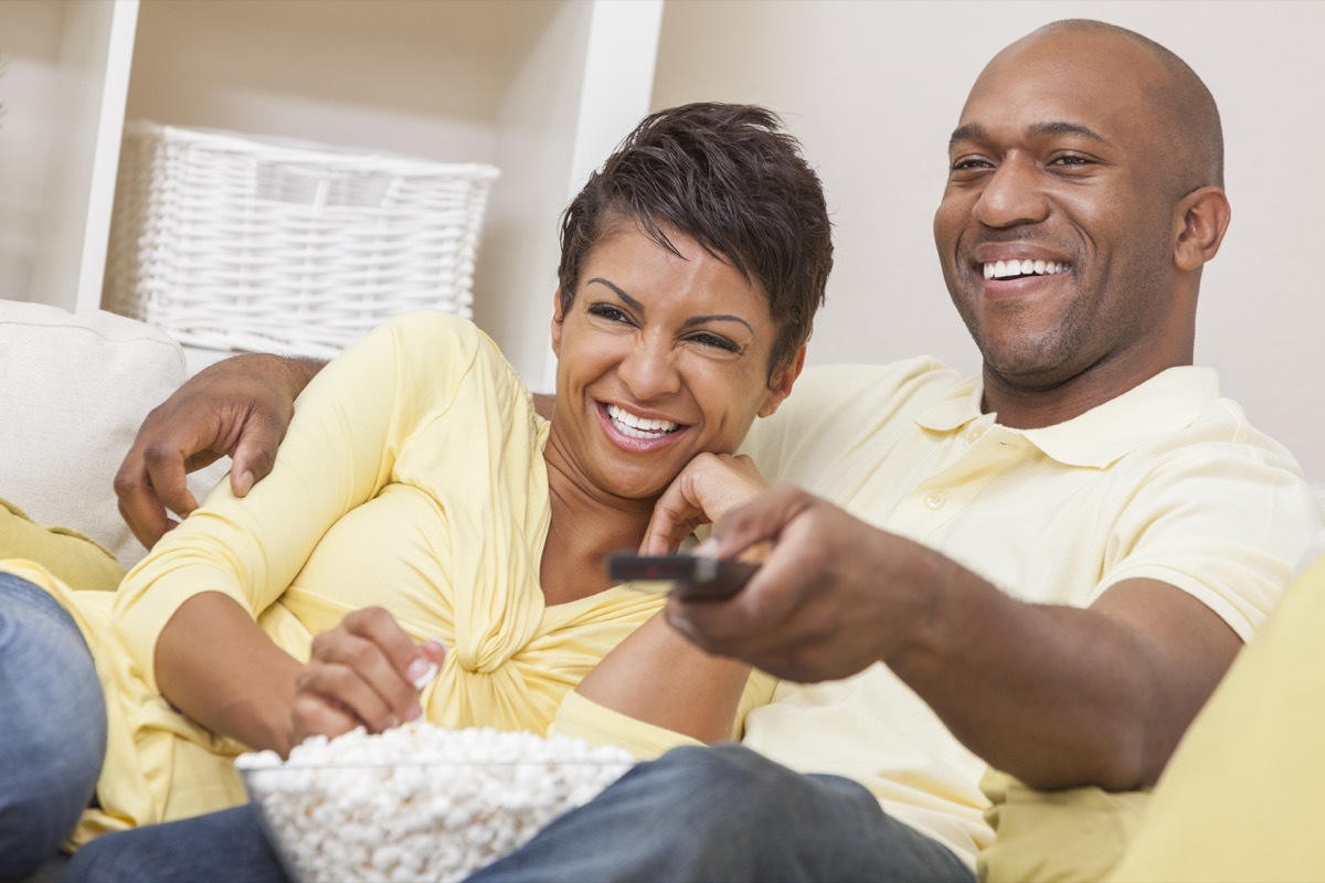Black couple watching television with a remote on the couch