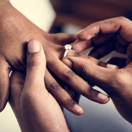 Man putting a wedding ring on his new wife