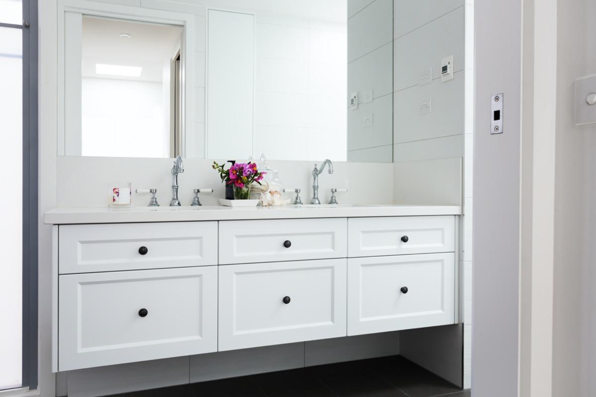 white bathroom vanity with round black knobs