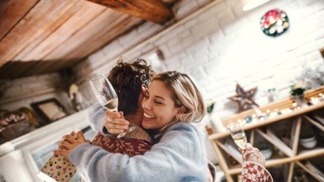 30-something white woman hugging her boyfriend and holding a glass of champagne