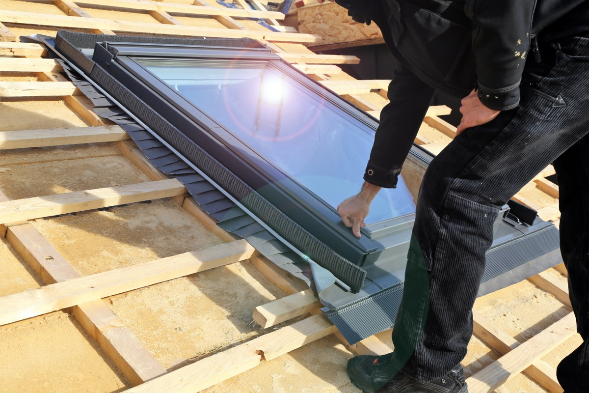 white man in black clothing installing a skylight on roof