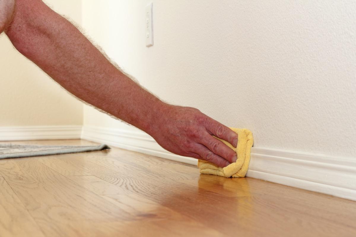 white hand wiping baseboard