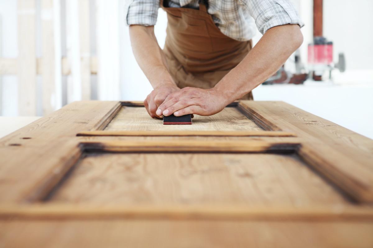 white man sanding wooden door