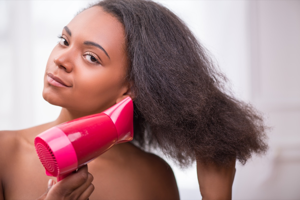Black woman using a blow dryer on her hair