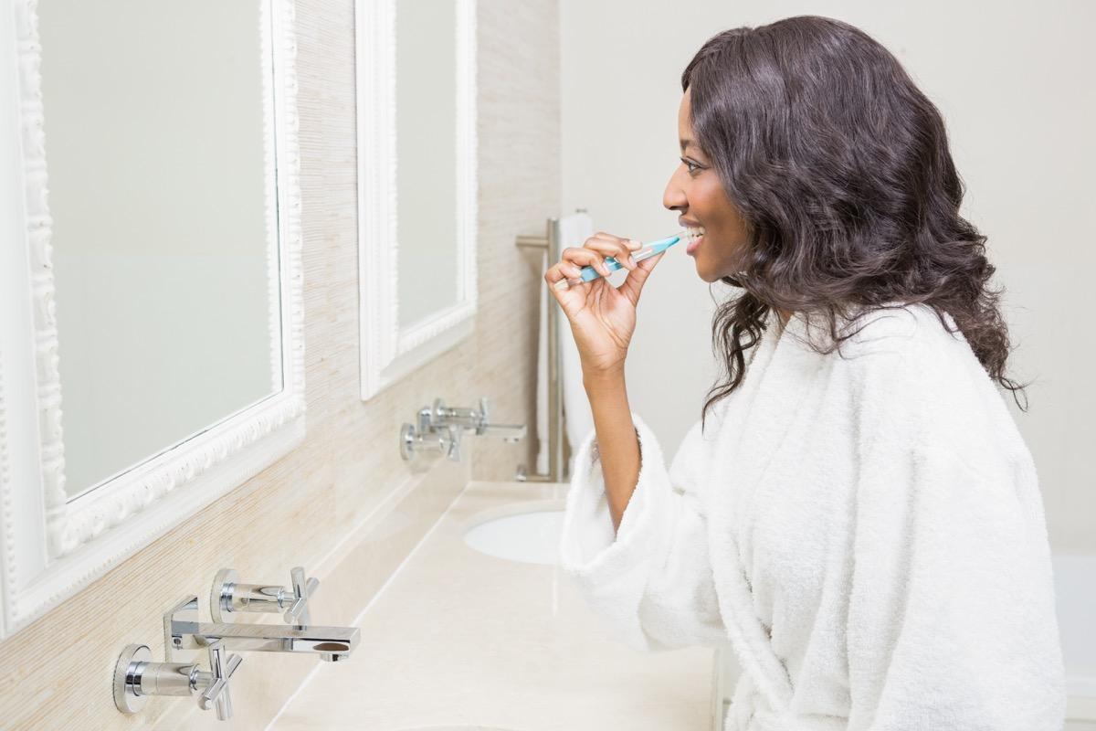 Black woman brushing her teeth in the bathroom