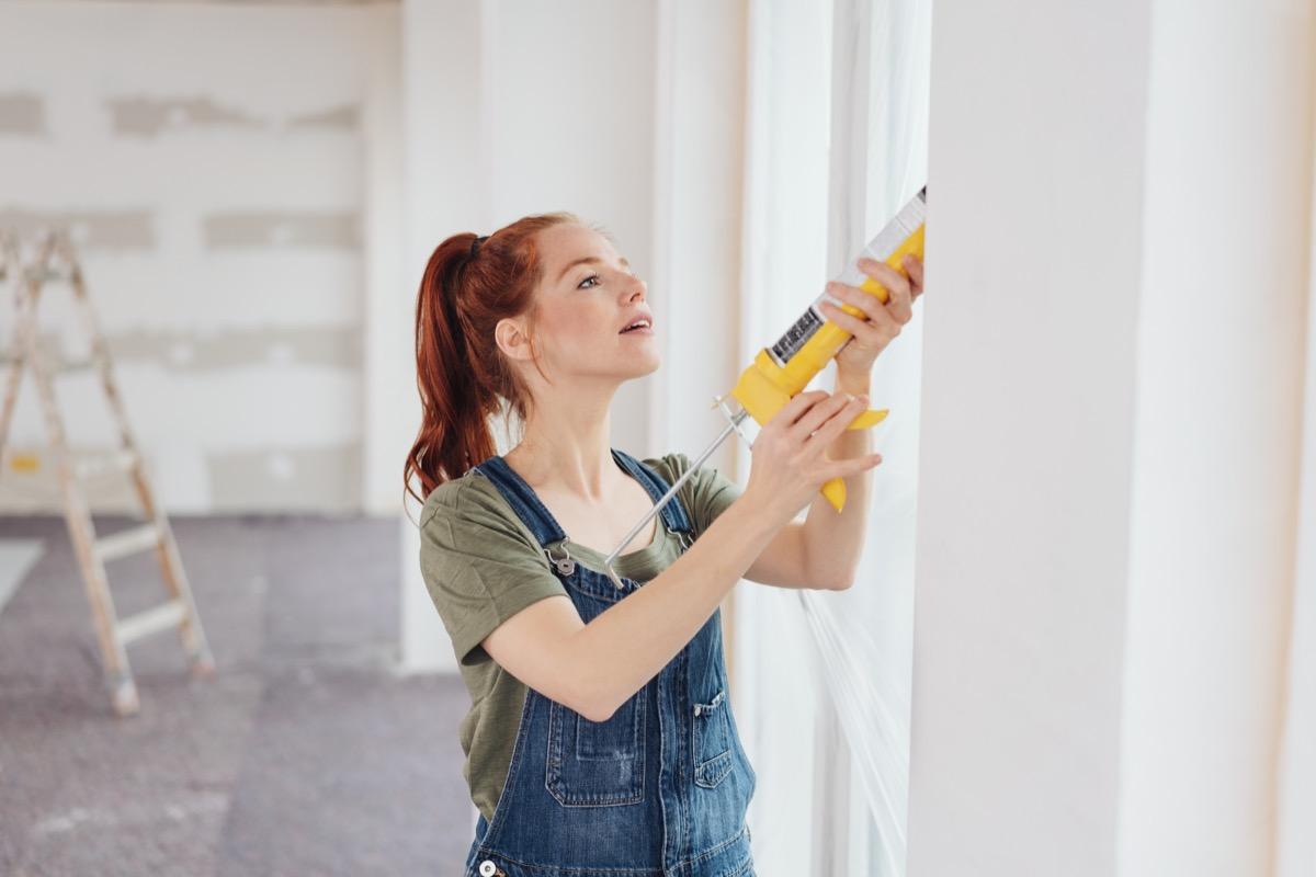 redheaded woman caulking window