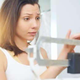Woman schecking the scale with a concerned look on her face