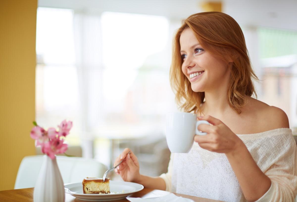 Red-headed woman enjoying a sugary dessert