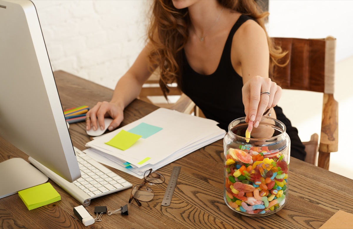 Woman mindlessly eating a jar of gummy candy while working on her desktop computer
