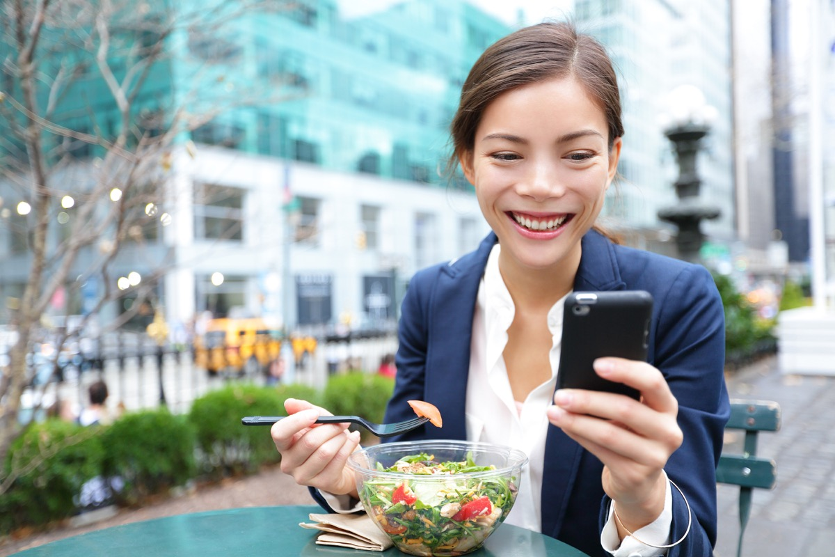 Woman smiling while eating a salad for lunch alone looking at her phone