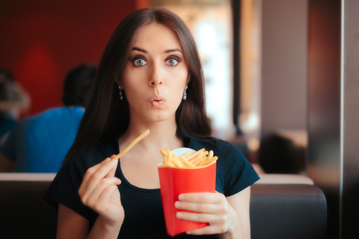 Woman eating salty french fries