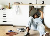black woman laying down on floor fixing pipes under kitchen sink