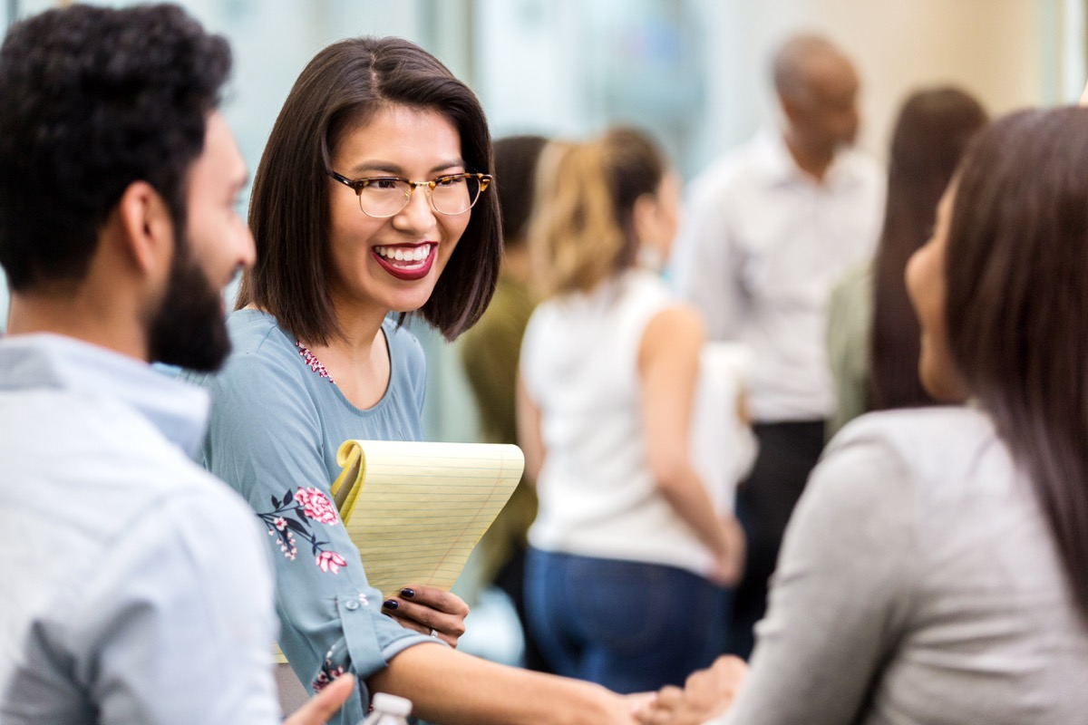 cheerful young businesswoman stands with an unrecognizable coworker in a crowded office building and smiles as she shakes hands with her new unrecognizable client
