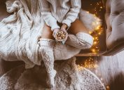 woman sitting on bed next to twinkly lights and hot chocolate