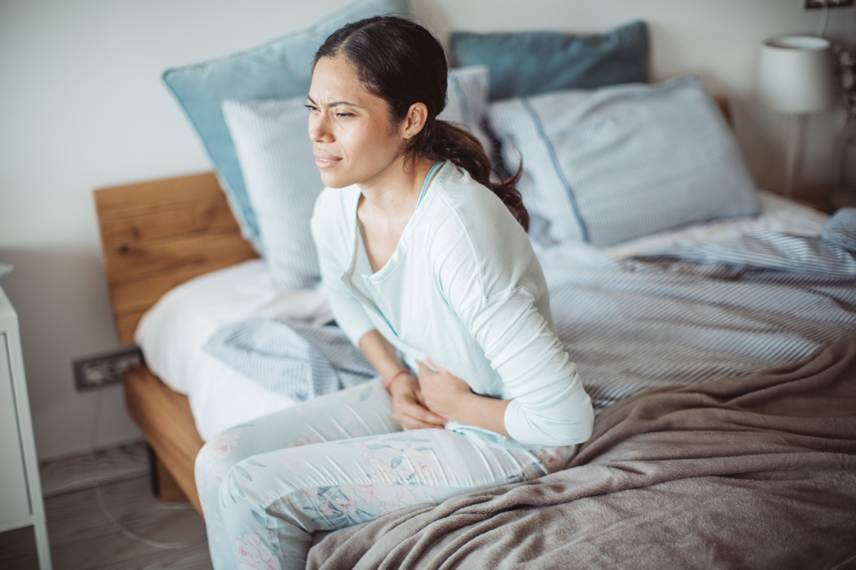 Woman holding her stomach in pain sitting on edge of bed