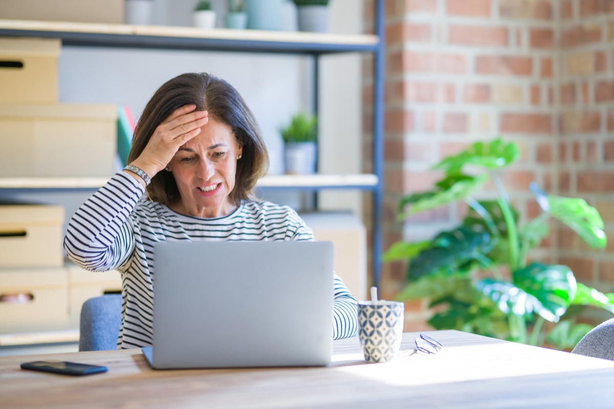 Woman on a laptop looking stressed and angry