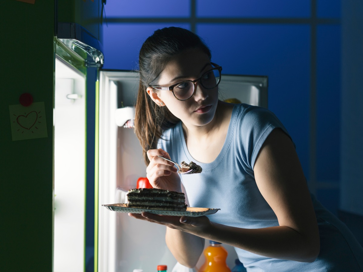 Woman sneaking into the fridge for a late night snack of cake hoping not to get caught