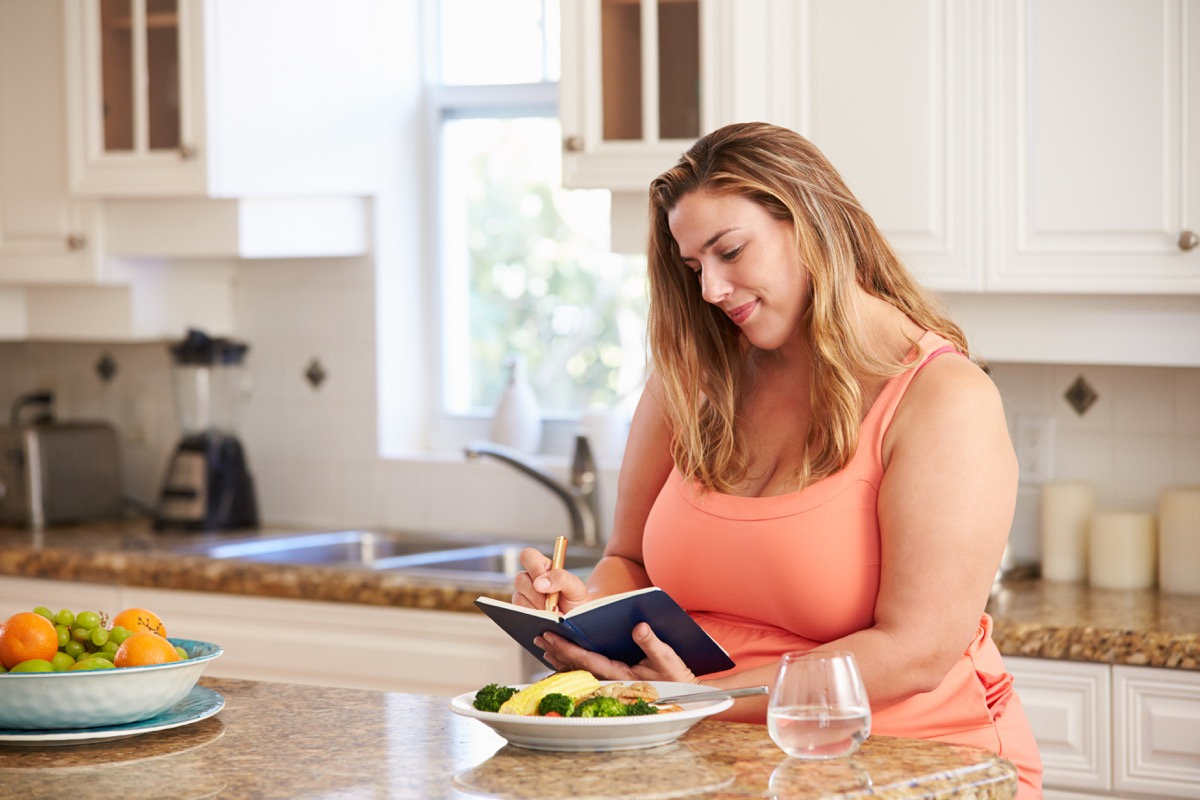 Woman writing in food log journal before eating her meal