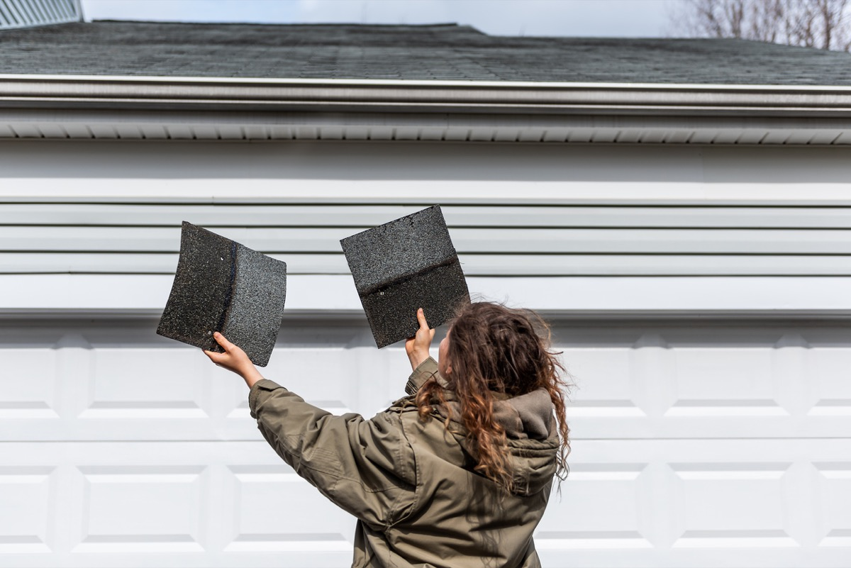 Female homeowner standing in front of house holding two roof tile shingles inspecting damage